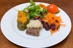 Vegetarische Vegietaler mit Roggenbrot aus Vollkorngetreid und buntem Salat auf einem weißen Teller