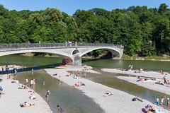 Stadtbewohner auf München suchen Abkühlung an heißen Sommertagen und baden in dem bayrischen Fluß Isar, in München