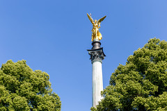 Close-up of a golden angel of peace on a white pillar Prinzregentstraße in front of the blue sky, in Munich - Bavaria, Germany