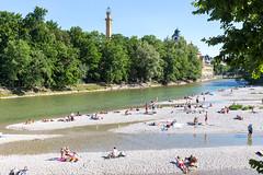 Stadtbewohner nutzen den Isar-Fluß als öffentliches Freibad und sonnen sich am heißen Sommertag in München auf dem steinigen Flußbett