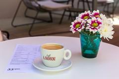 Eine Tasse Kaffee, neben Sommerblumen, auf der Terrasse eines Cafés