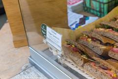 Belegte Vollkorn-Sandwichscheiben mit Fleisch und Avocado, hinter Glas in einer Auslage