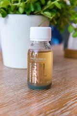 Gesunder Spirulina-Ingwershot-Drink in einem Glasfläschchen, der gesunden Fast-Food-Kette dean&david