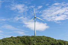Erneuerbare Energien mit einem einzelnen Windkraftrad auf einem Berg, vor blauem Himmel, das Windenergie in elektrische Energie umwandelt
