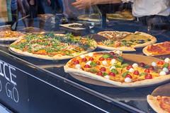 Pizzeria verkauft große bunte Pizzastücke zum Mitnehmen und stellt sich im Schaufenster aus