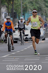 Athlete runs the marathon, next to two cyclists, with the picture title Cologne Marathon 2020