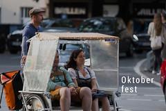 Fahrradtaxi für zwei Oktoberfest-Besucher in bayrischer Lederhose und Dirndl - Tracht
