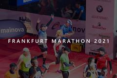 Erfolgreiche Marathonläufer überqueren glücklich die Ziellinie, neben Zuschauern, mit dem Bildtitel Frankfurt Marathon 2021