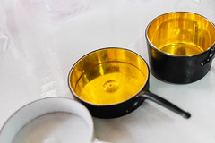 Miniature pans and pots on white surface