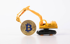 Yellow digger with golden Bitcoin
