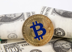 Golden Bitcoin with dollar banknotes