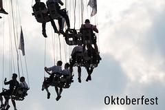 Männer in Lederhosen und Trachtenkostüm auf einem Kettenkarussell, während des Oktoberfest in München