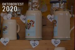 """O' zapft is in München, mit rustikalen Bierkrüge am Souvenirstand, neben dem Bildtitel """"Oktoberfest 2020"""""""