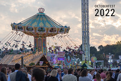 Traditional Bavarian folk festival with chairoplane and visitors, next to picture title Oktoberfest 2022