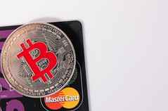Silver Bitcoin with black credit card