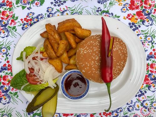 Wagyu-Burger mit Salat, Gurken, Zwiebeln, Tomaten, Chili-Paprika, Pommes frites und Barbecue Soße auf weißem Teller