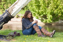 Woman sat by river wearing country leather boots