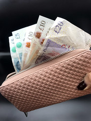 An array of £5, £10 and £20 UK sterling notes in a purse, stock photo