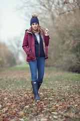Woman walking in woodland wearing jacket and wool hat
