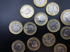 UK £1 coins in the new style across a black background, stock photo