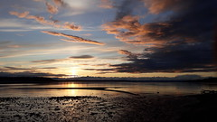After the rain, sunset over South Puget Sound, dark rainclouds, tide rising slowly, driftwood, colors, South Des Moines, Washington, USA