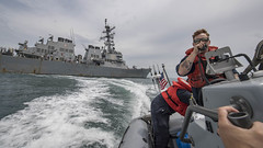 A Sailor uses the radio aboard a rigid-hull inflatable boat to communicate with the bridge