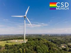 """Ein Windrad nahe der Allianzarena in München, neben einer Regenbogenflagge und dem Bildtitel """"CSD Munich"""", um den Christopher Street Day zu feiern"""