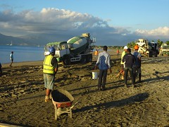 Fiji. Denarau Island. A bogged cement truck on the beach in front of the Sofitel resort is pulled out successfully by another cement truck.