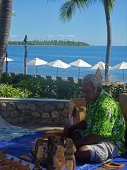 Fiji. Denarau Island.  A Fijian man demonstrates wood carving beside the beach at the Sofitel resort.