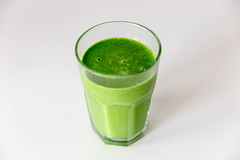 Green Smoothie drink in a glass on a white table