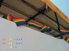 Wehende LGBTQ-Flaggen in Regenbogenfarben auf einem Parade-wagen während des Christopher Street Day in Köln