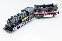Black toy locomotive with a wagon on a white background