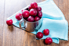 Fresh plums in an iron mug on the wooden background with a blue kitchen towel