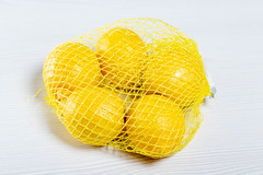 Ripe yellow lemons Packed in mesh