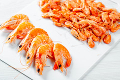 Boiled shrimp of different sizes on white background