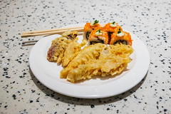 Japanese tempura and maki sushi on white plate