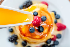 Closeup of honey pouring on the pancakes with berries