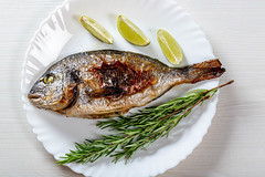 Whole baked Dorado fish on a white plate with fresh rosemary and lime slices
