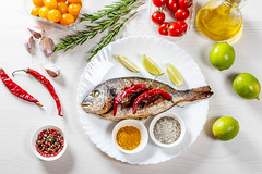 Top view baked Dorado fish with spices and vegetables on white wooden background