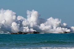 U.S. Marine Corps amphibious assault vehicles give off tactical smoke as they approach Langham Beach
