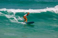 Girl in a bikini on a surf on a high wave. Nai Harn Beach, Phuket, Thailand                   XOKA5753bs