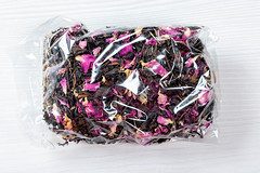 Dried Crimean black tea with pink flower petals in a package