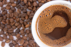Top view of Raw Coffee arround Cup of Black Coffee