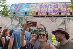 Two women taking a selfie with the 'Welcome to Tomorrowland' sign at Tomorrowland festival in Belgium