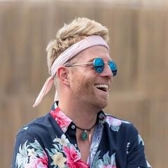 Portrait von Festivalbesucher in buntem Hippie-Look mit John-Lennon-Sonnenbrille am Tomorrowland