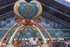 DJ spielt Musik innerhalb eines futuristischen DJ Stands während die Besucher in Schlangen warten um das Tomorrowland Festival zu betreten