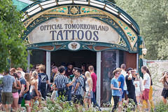 Festival people gather in front of the Official Tomorrowland Tattoos stage