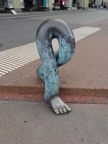 escultura de bronce dos piernas bajando la acera obra de Luciano Andreani Berna Suiza