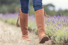 Woman walking through lavender field in suede country boots