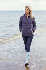 Woman walking on the beach in padded jacket
